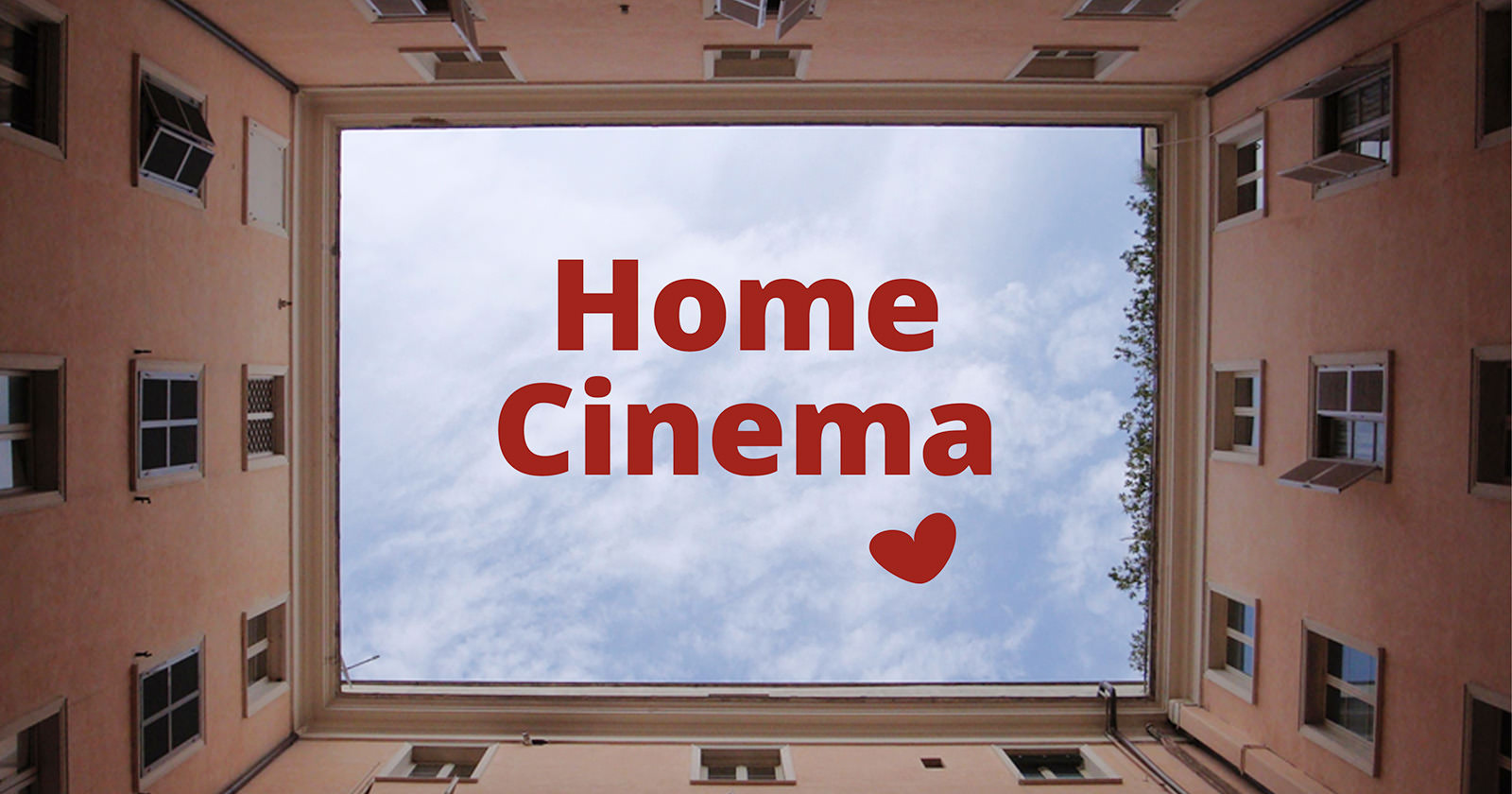 Eine Häuserschlucht von unten Fotografiert, damit der Himmel aussieht wie eine Leinwand. im Himmel steht der Text Home Cinema und ein Herz